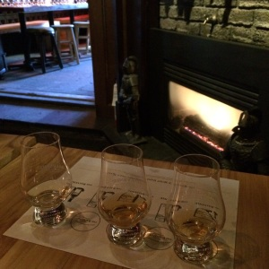 A flight of single-malt scotches on a fireside table.