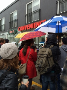 A group of people with umbrellas gathered outside a Queen Street West convenience store