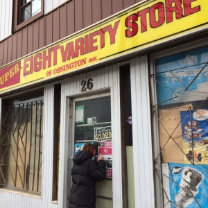 A woman peeks in the window of the now-boarded-up Eight Variety Store