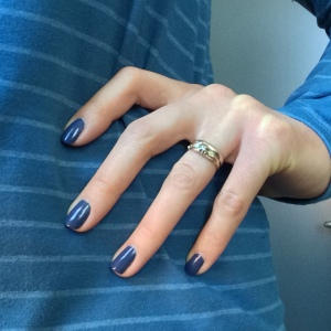 Blue-painted fingernails against a blue striped shirt